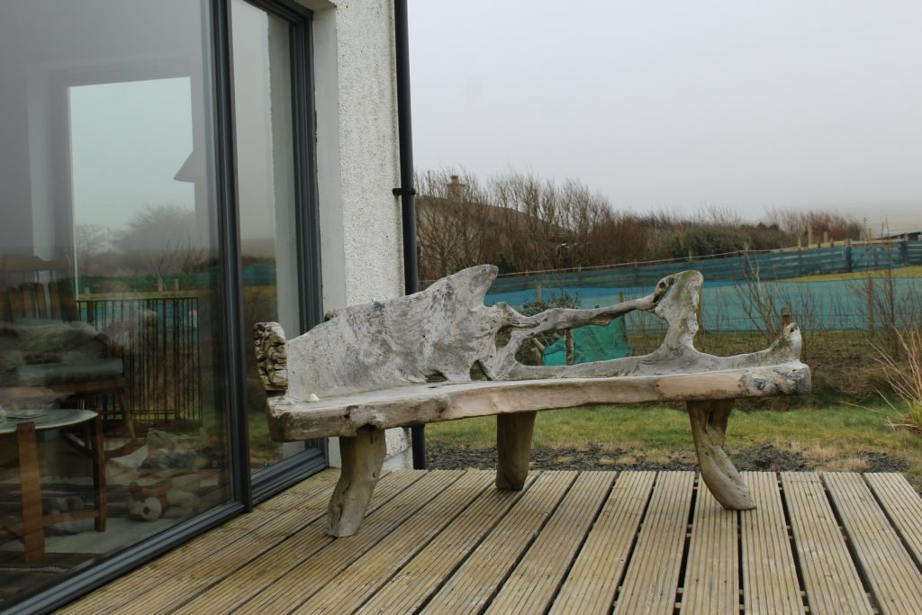 A drift wood chair at the back of the cottage. the back walls are full glass.